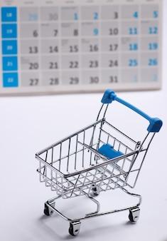 白い背景の上のデスクトップカレンダーとミニチュアショッピングカート。ホリデーショッピング、ブラックフライデー、毎月の特別オファーのコンセプト