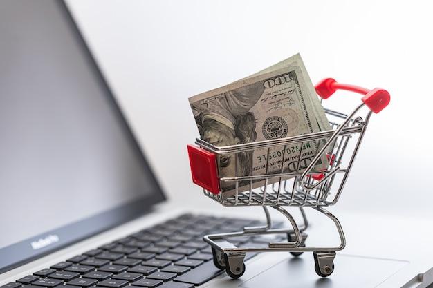 Миниатюрная тележка для покупок с долларовой банкнотой внутри. концепция покупок в интернете и электронной коммерции.