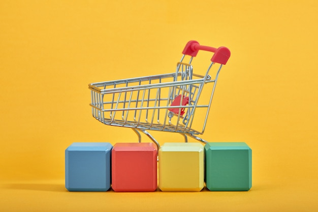 A miniature shopping cart and wooden blocks with the wordings sale, isolated against mint background.
