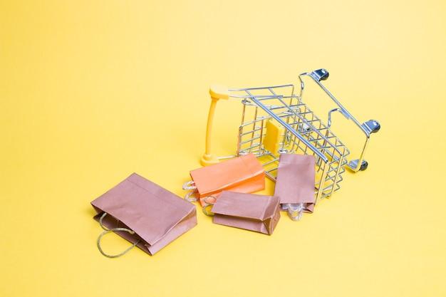 노란색 바탕에 미니어처 쇼핑 트롤리