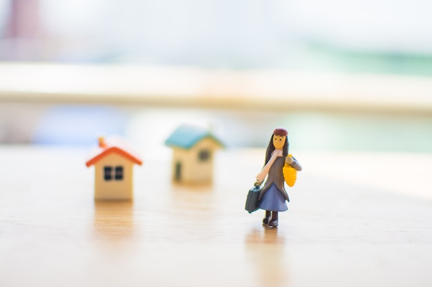 Miniature of single woman with home on wooden table. subject is blurred.
