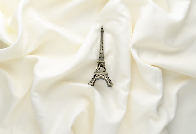 Miniature statuette of the eiffel tower on a white silk background. trend minimalism souvenir from paris. top view.