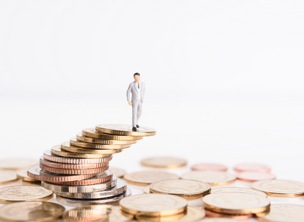 Miniature successful business people stand on top of golden money coins isolated on white background, high risk high return concept