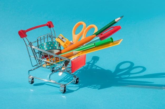 Miniature supermarket trolley with stationery inside: scissors, pens, pencils, paper clips, ruler, tape. blue background, copyspace.