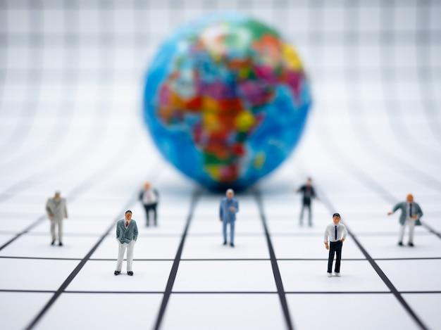 地球儀を持ったビジネスマンのミニチュアチームが、隔離中に自宅から、また社会的距離から作業します。自己分離、ビジネス、在宅勤務、社会的距離、コロナウイルス、covid-19コンセプト。