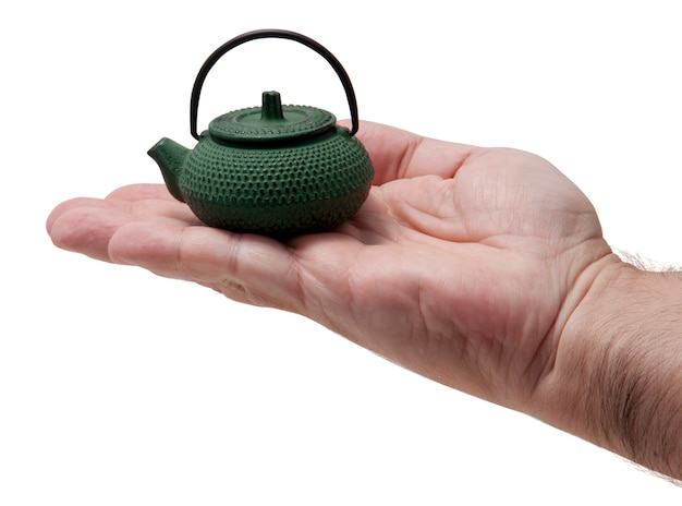Миниатюрный чайник на ладони с белым фоном