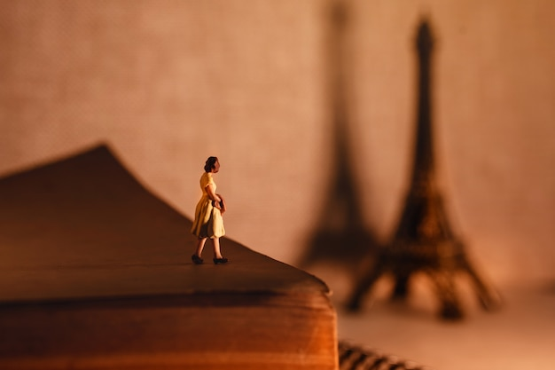 Miniature tourist woman standingon the aged book and looking at the eiffel tower.