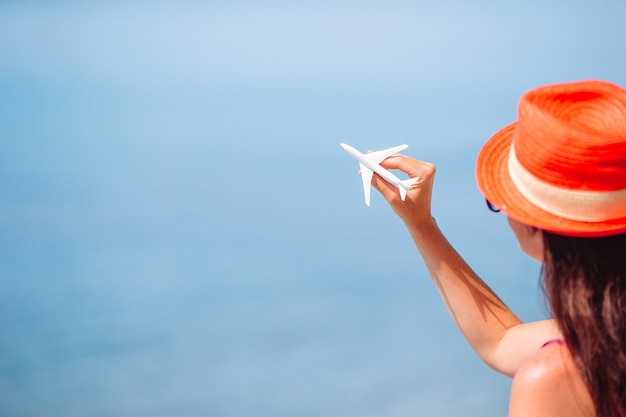 Miniature toy airplane in female hands. trip by airplane. conceptual image for travel and tourism.
