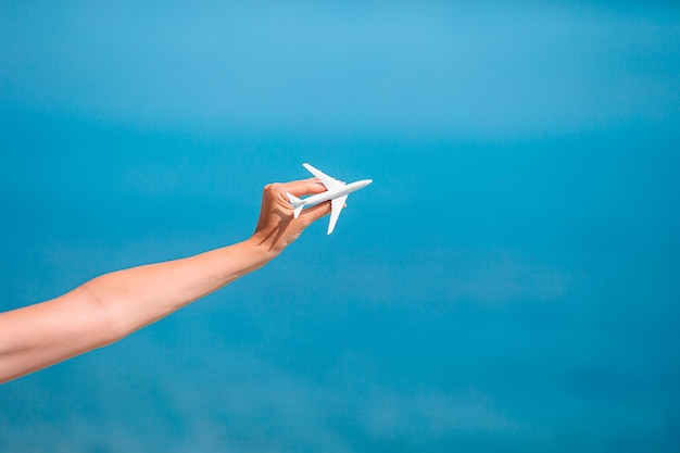 女性の手の中のミニチュアおもちゃの飛行機。飛行機での旅行。旅行と観光の概念図。