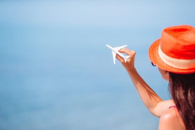 Миниатюрный игрушечный самолетик в женских руках. поездка на самолете. концептуальный образ для путешествий и туризма.