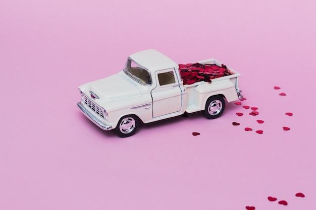 Miniature toy car delivering red hearts confetti for valentine's day on pink background