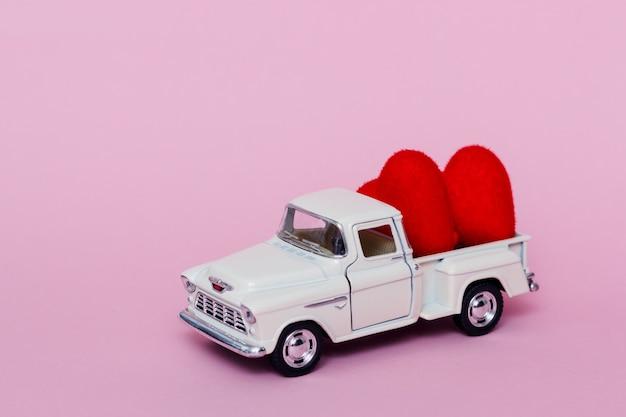 ピンクのテーブルでバレンタインデーに赤いハートを届けるミニチュアおもちゃの車