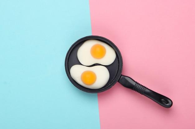 핑크 블루 파스텔 배경에 튀긴 계란 미니어처 장난감 프라이팬. 평면도. 미니멀리즘 음식 개념, 아침 식사. 스튜디오 촬영