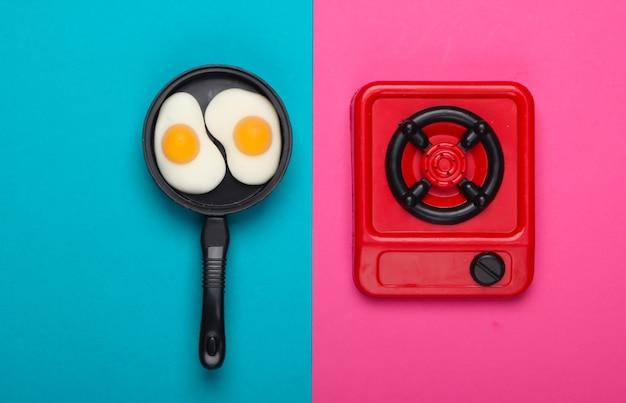난로에 튀긴 계란 미니어처 장난감 프라이팬. 분홍색 파란색 배경입니다. 평면도. 미니멀리즘. 스튜디오 촬영