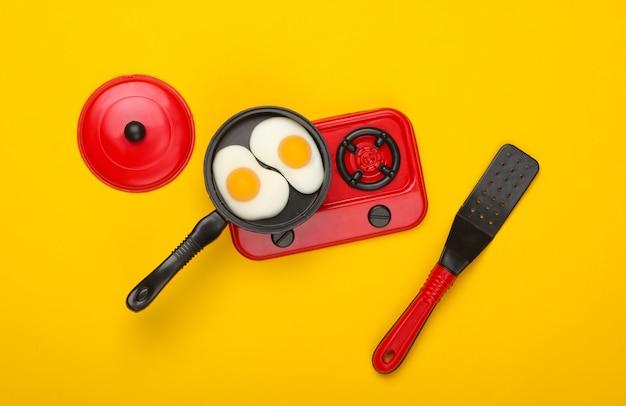 난로에 튀긴 계란 미니어처 장난감 프라이팬. 노란색 배경. 평면도. 미니멀리즘. 스튜디오 촬영