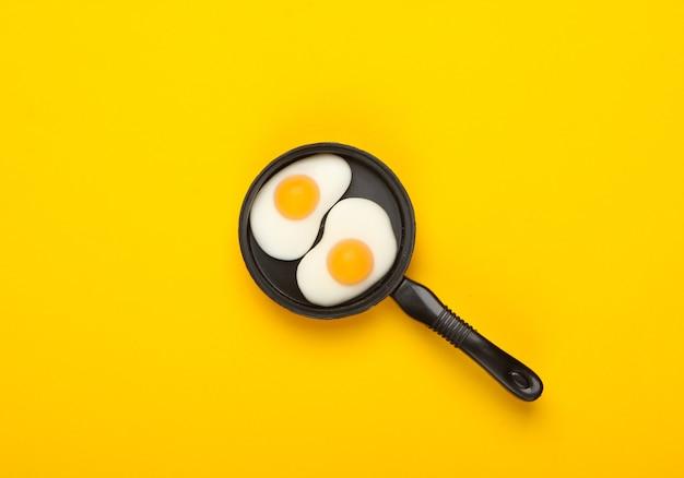 노란색 바탕에 튀긴 계란 미니어처 장난감 프라이팬. 평면도. 미니멀리즘 음식 개념, 아침 식사. 스튜디오 촬영