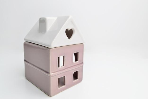 Миниатюрный игрушечный модельный домик на белом фоне. концепция экологии сладкого дома страхования недвижимости ипотеки.