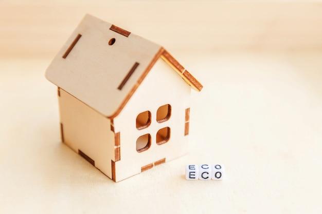 木製の背景に碑文eco文字単語のミニチュアグッズモデル家。エコビレッジ、抽象的な環境背景。生態学ゼロ廃棄物社会責任リサイクルバイオホームコンセプト