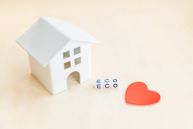 Miniature toy model house with inscription eco letters word on wooden backdrop. eco village, abstract environmental background. ecology zero waste social responsibility recycle bio home concept