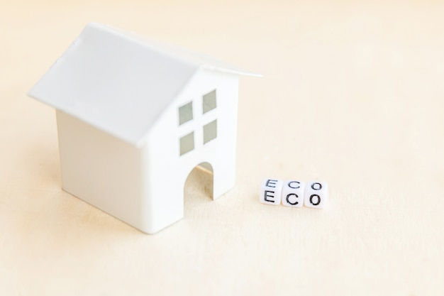 Miniature toy model house with inscription eco letters word on wooden background