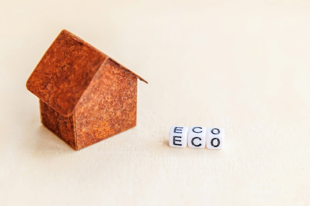 Miniature toy model house with inscription eco letters word on wooden surface. eco village. ecology zero waste social responsibility recycle bio home concept