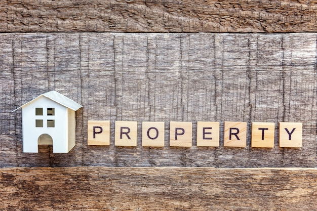Miniature toy model house with inscription property letters word on wooden background