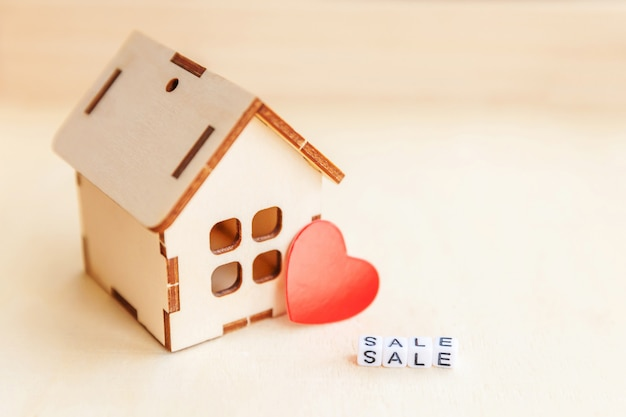 Miniature toy model house with inscription sale letters word on wooden background