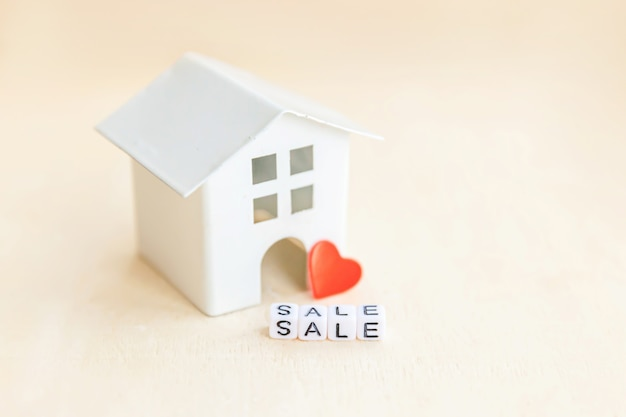 Miniature toy model house with inscription sale letters word