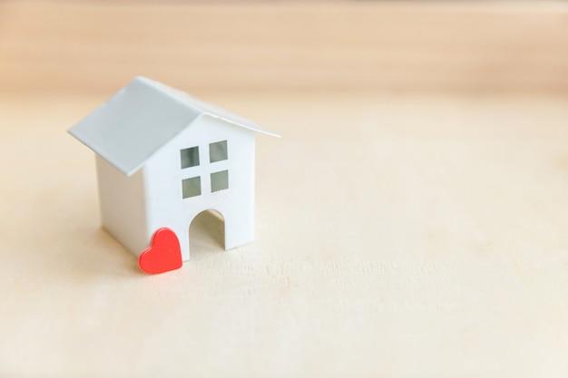 木製の背景に赤いハートのミニチュアグッズモデル家。エコビレッジ抽象的な環境背景。不動産住宅ローンの財産保険の甘い夢の家の生態学の概念