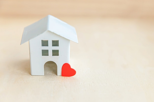 Miniature toy model house with red heart on wooden backdrop