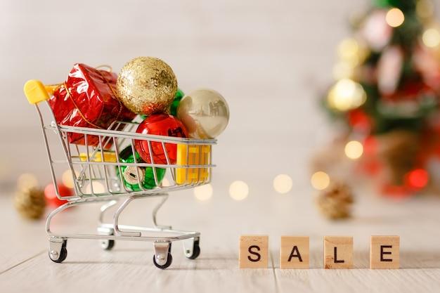 Миниатюрная игрушечная тележка для супермаркета. концепция рождественской распродажи