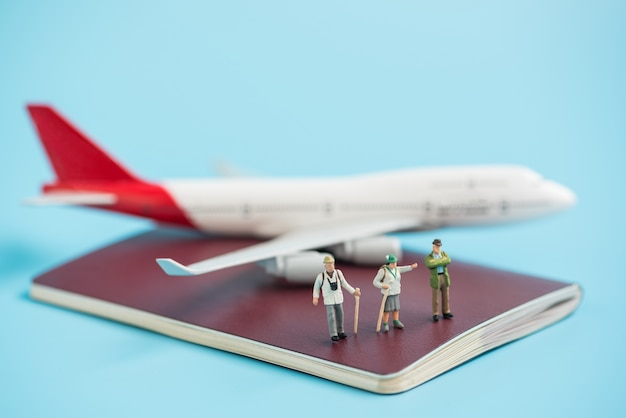 Miniature traveler and airplane model on passport book