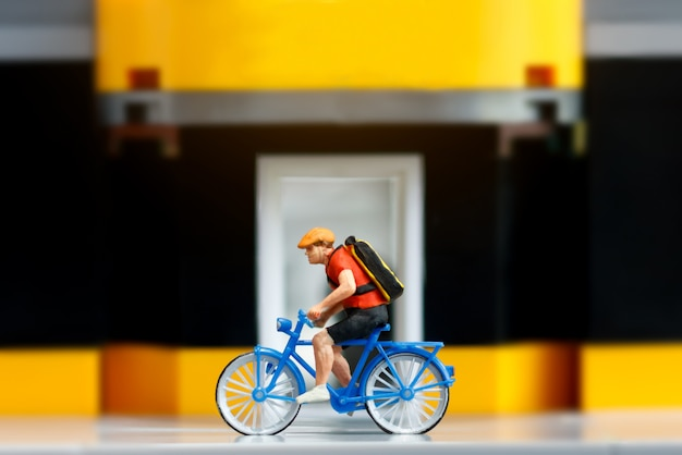 Miniature traveler riding bicycle with sports shop.
