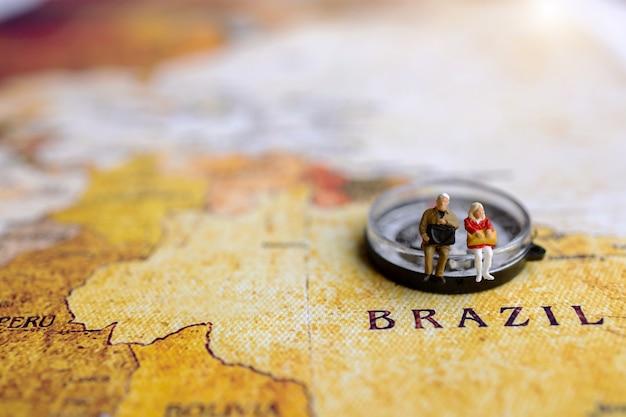 コンパスとヴィンテージの世界地図に座っているバックパックを持つミニチュア旅行者。旅行のコンセプト。