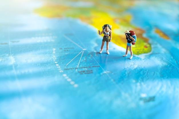 世界地図上に立っているバックパックを持つミニチュア旅行者。旅行のコンセプト。
