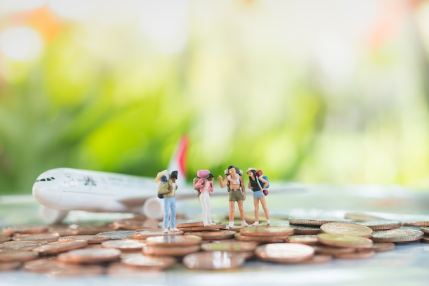 Miniature of travelers are standing on pile of coins