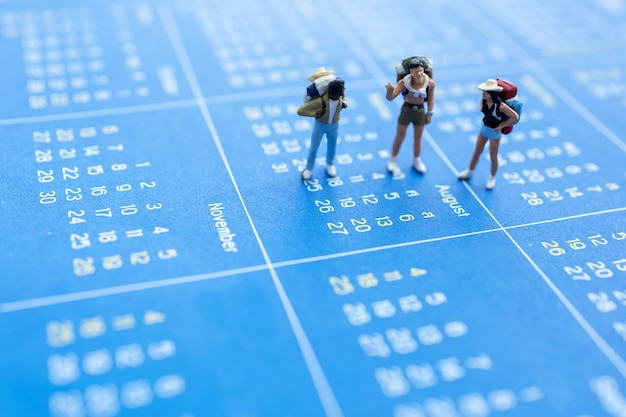 Miniature travelers with a backpack standing on calendar, travel and vacation concept.