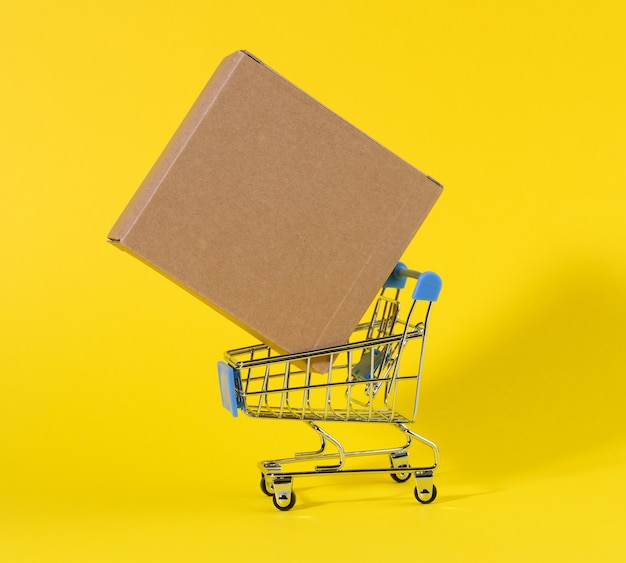 Miniature trolley with brown cardboard box on yellow surface. the concept of delivery of goods, online shopping