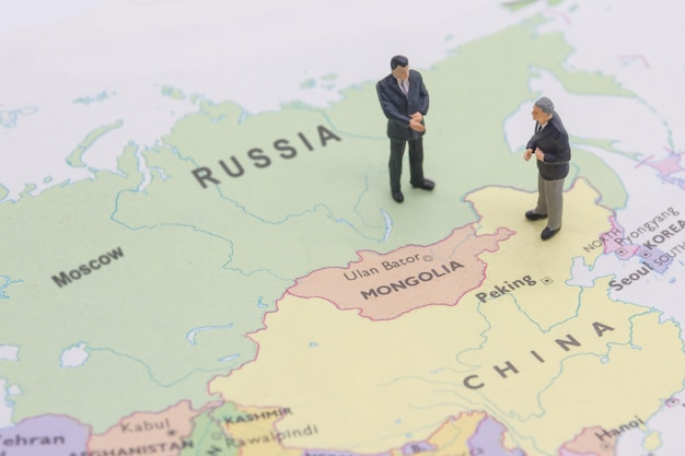 Miniature two businessman shakehand on china and russian map