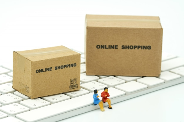 Miniature two people sitting on white keyboard online shopping