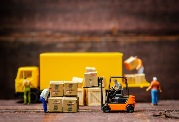 Miniature warehouse workers forklift carrying goods box to semi truck with trailer