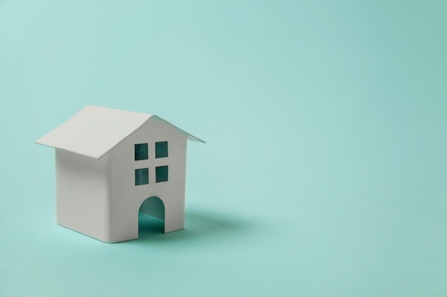 Miniature white toy house on blue background