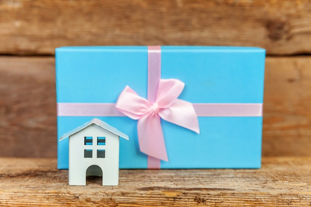 Miniature white toy house and gift box on wooden background