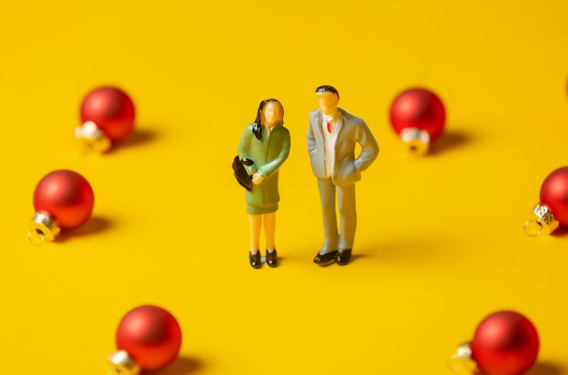 Miniature woman and man figures stand surrounded by red christmas baubles on yellow surface