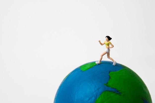 Miniature woman running on globe on white