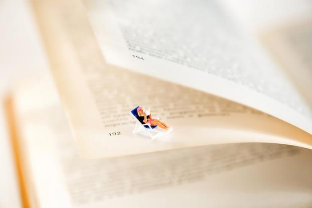 Миниатюрная женщина сидит между страницами книги