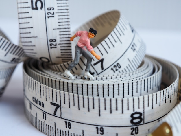 Miniature woman skating on measuring tape, thinking of weight loss and slim body.