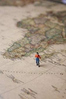 Miniature woman on vintage world map