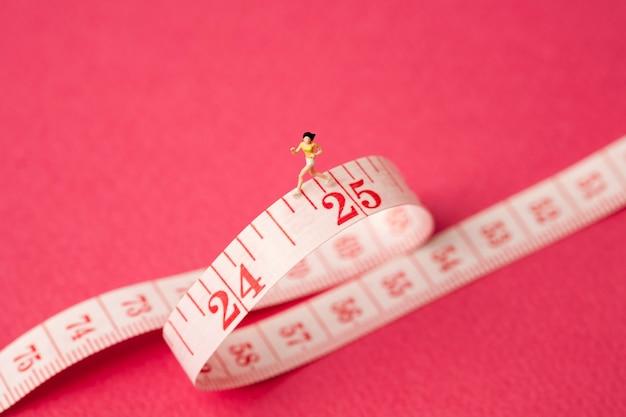 분홍색 배경에 측정 테이프를 가진 미니어처 여자