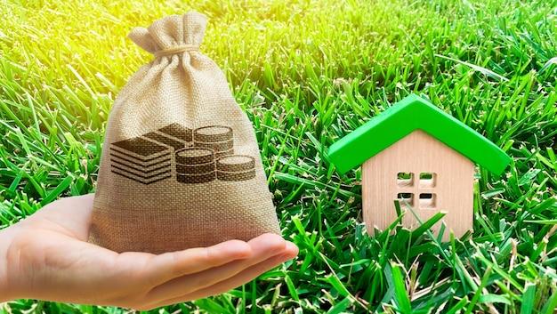 Миниатюрный деревянный дом и денежный мешок на траве.
